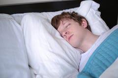 Молодой человек спать в кровати - конце-вверх Стоковые Изображения