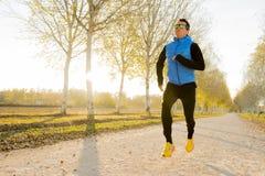 Молодой человек спорта бежать outdoors в с следе дороги смолол с деревьями под красивым солнечным светом осени Стоковые Фотографии RF