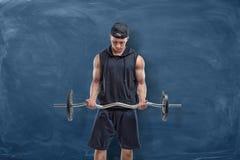 Молодой человек спорта держа серебряную штангу в его руках во время тренировки на голубой предпосылке доски Стоковые Фотографии RF