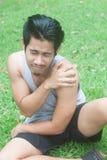 Молодой человек спорта имея боль плеча в природе Стоковое Изображение RF
