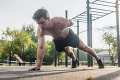 Молодой человек спортсмена делая тренировку нажима-вверх одн-руки разрабатывая его верхнее тело muscles снаружи в лете Стоковое Изображение RF