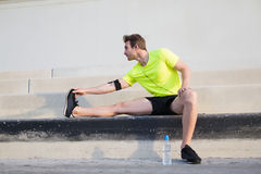 Молодой человек спорт предупреждая вверх перед его начинает утром, который побежали outdoors на рано утром Стоковое Изображение RF
