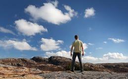 Молодой человек стоит на скалистой земле Стоковое Фото