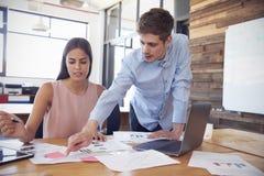 Молодой человек стоит работающ с женщиной на ее столе в офисе стоковое изображение