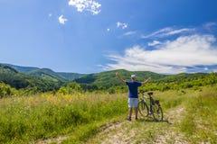 Молодой человек стоя близко велосипед в восходе солнца утра с wonderf Стоковые Фотографии RF
