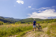 Молодой человек стоя близко велосипед в восходе солнца утра с wonderf Стоковые Изображения RF