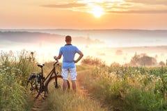 Молодой человек стоя близко велосипед в восходе солнца утра с wonderf Стоковые Изображения