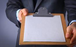 Молодой человек стоя при папка, изолированная на серой предпосылке Стоковые Фотографии RF