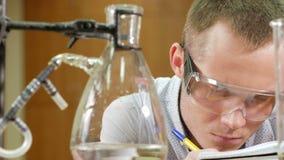 Молодой человек студента работая с химикатами и пишет результаты в университете Защитные стекла и отсутствие роба Beakers и сток-видео