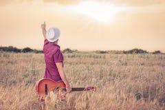 Молодой человек с акустической гитарой наслаждаясь заходом солнца стоковое изображение