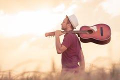 Молодой человек с акустической гитарой outdoors стоковые изображения rf