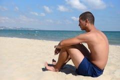 Молодой человек с атлетическим телом в голубых шортах стоя на песке стоковые изображения rf