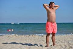 Молодой человек с атлетическим телом в розовых шортах стоя с его ба Стоковое Изображение RF