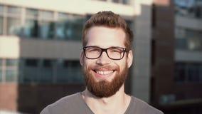 Молодой человек с бородой и стекла стоя в улице и смотря камеру Гай серьезно смотрит и после этого начинает усмехнуться акции видеоматериалы