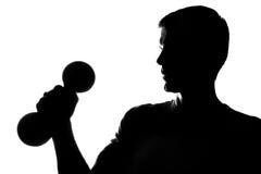 Молодой человек с гантелями в руке Стоковые Фото
