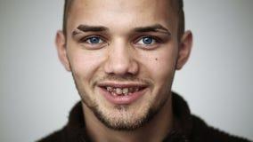 Молодой человек с голубыми глазами усмехаясь и показывая расчалки на зубах и подмигивать сток-видео