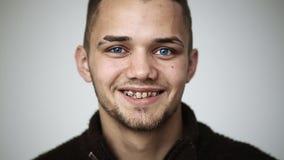 Молодой человек с голубыми глазами усмехаясь и показывая расчалки на зубах и подмигивать акции видеоматериалы