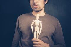 Молодой человек с деревянной куклой Стоковое фото RF