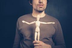 Молодой человек с деревянной куклой Стоковая Фотография