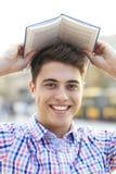 Молодой человек с книгой над его головой стоковое изображение