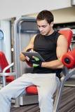 Молодой человек с компьютером ПК таблетки в спортзале Стоковая Фотография