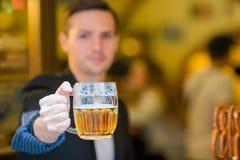 Молодой человек с пивом и посоленными мягкими кренделями в баре спорта пива стоковые изображения