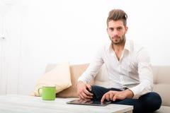 Молодой человек с ПК таблетки на софе Стоковые Изображения