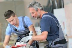 Молодой человек с профессиональным слоем кирпича в училище Стоковое Фото