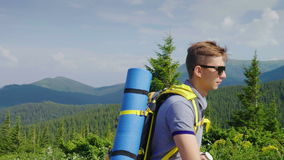 Молодой человек с рюкзаком поднимает гористый Портрет здорового и счастливого туриста в горах акции видеоматериалы