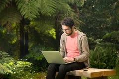 Молодой человек с сидеть компьтер-книжки и smartphone внешний в парке Стоковые Фотографии RF