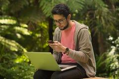 Молодой человек с сидеть компьтер-книжки и smartphone внешний в парке Стоковые Фото