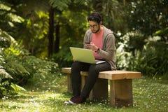 Молодой человек с сидеть компьтер-книжки и smartphone внешний в парке Стоковая Фотография
