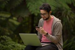 Молодой человек с сидеть компьтер-книжки и smartphone внешний в парке Стоковое фото RF