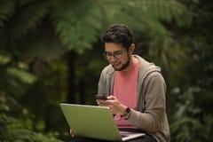 Молодой человек с сидеть компьтер-книжки и smartphone внешний в парке Стоковое Фото