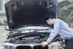 Молодой человек с сломленным автомобилем на дороге Стоковые Изображения RF