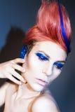 Молодой человек с тенями голубого глаза, голубые уши и розовые волосы с голубой стренгой на ей смотря камеру и руки приближают к  Стоковое Фото