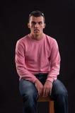 Молодой человек сдуру, усаженный на стул стоковое фото
