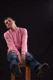 Молодой человек сдуру, усаженный на стул стоковое фото rf