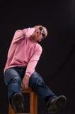 Молодой человек сдуру, усаженный на стул стоковая фотография
