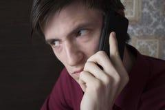 Молодой человек с черным smartphone, с тревожным подозрительным взглядом Стоковая Фотография RF