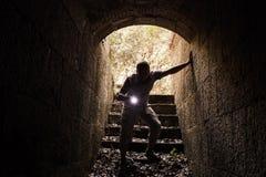 Молодой человек с электрофонарем входит в каменный тоннель Стоковое Изображение RF