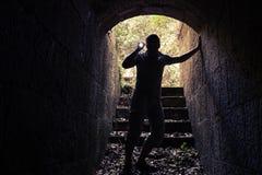 Молодой человек с электрофонарем входит в темный каменный тоннель Стоковая Фотография RF