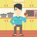 Молодой человек с яблоком в кухне Стоковое Изображение