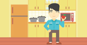 Молодой человек с яблоком в кухне Стоковые Изображения