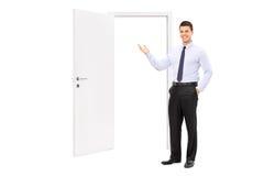 Молодой человек указывая к раскрытой двери Стоковое фото RF