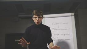 Молодой человек указывая на flipchart пока дающ представление к его коллегам видеоматериал