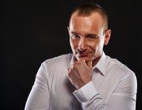 Молодой человек думая с пальцем около его усмехаться стороны стоковые фото