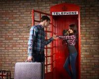 Молодой человек умоляя его жену для того чтобы получить с телефона Стоковые Изображения
