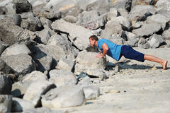 Молодой человек уносит нажим-поднимает среди камней стоковые фотографии rf