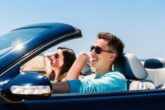 Молодой человек управляя с подругой в автомобиле с откидным верхом Стоковое Изображение RF